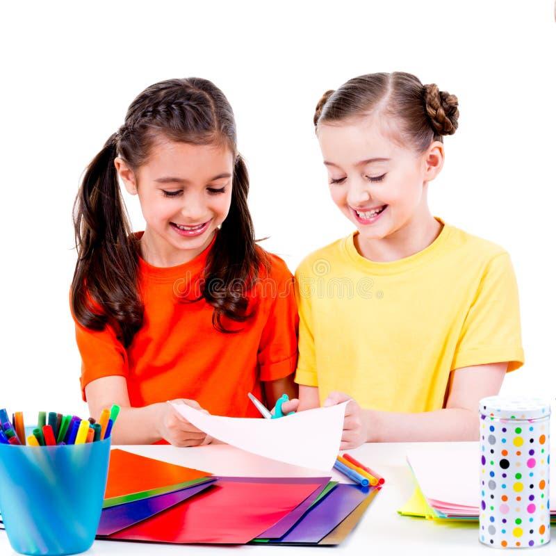 Gulliga små flickor i färgglat t-skjorta snitt scissor papp arkivbild