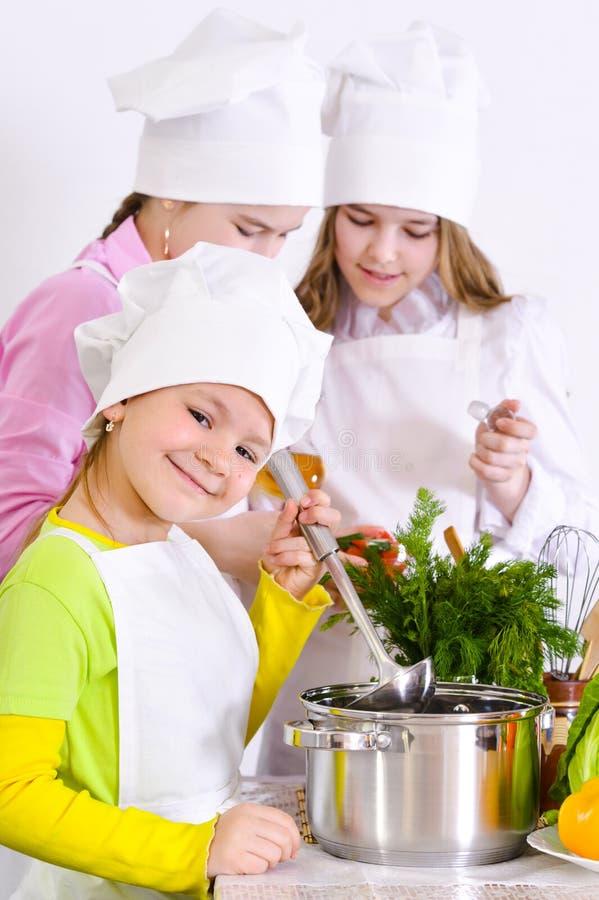 Gulliga små flickor i hattar och förkläden för kock` som s in förbereder matställen arkivfoto