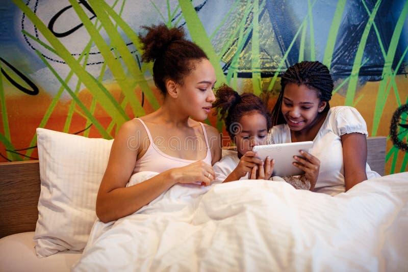 Gulliga små flickor och hennes moder som ligger på en säng arkivfoton