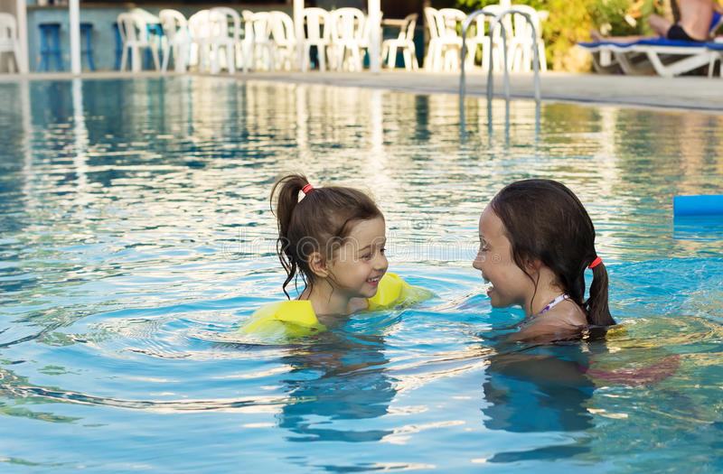 Gulliga små flickor som simmar i utomhus- pöl arkivbilder