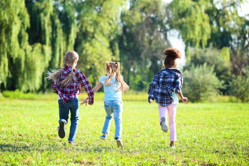 Gulliga små flickor som utomhus kör arkivfoton