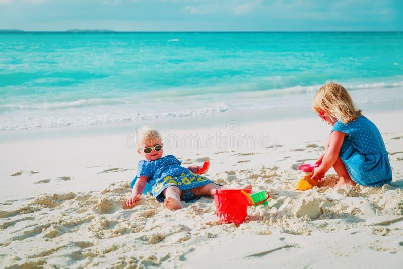 Gulliga små flickor spelar med sand på stranden arkivfoto