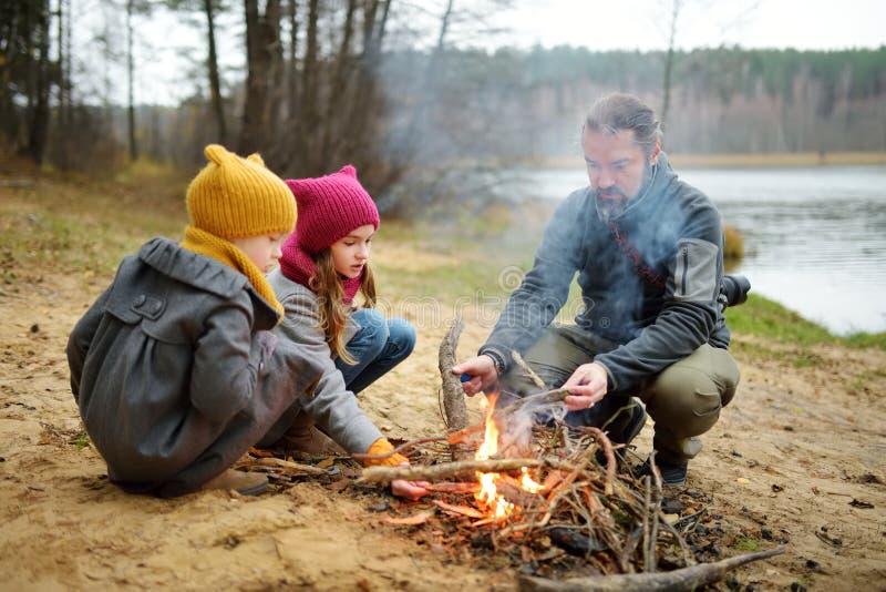 Gulliga små systrar och deras fader som sitter vid en brasa på kall höstdag Barn som har gyckel p? l?gerbrand Campa med ungar arkivbilder