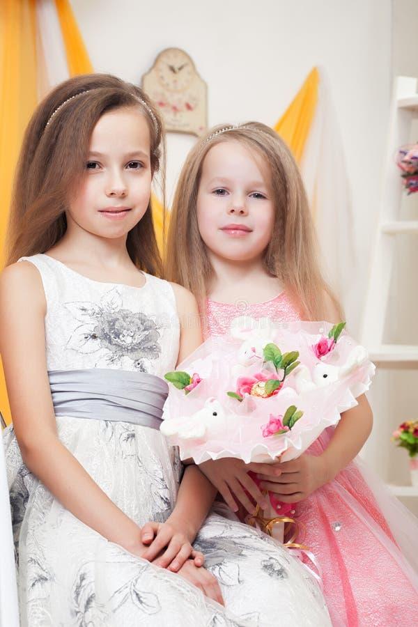 Gulliga små systrar som poserar med buketten av leksaker arkivbild