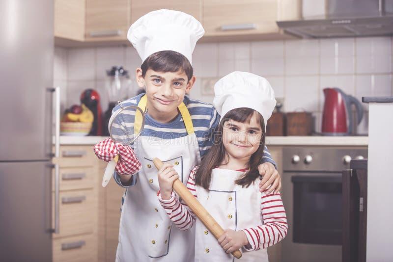Gulliga små ungar i köket fotografering för bildbyråer