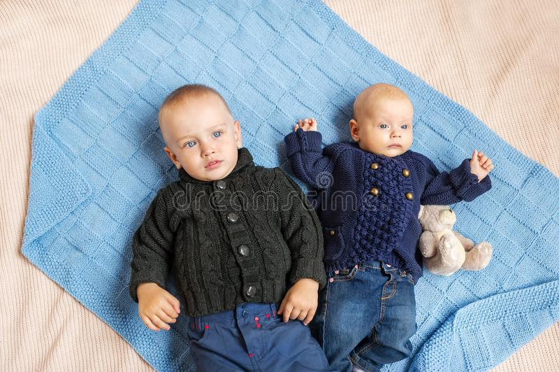 Gulliga små ungar i kläder som hemma ligger på säng Top beskådar royaltyfria foton