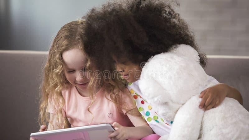 Gulliga små ungar som sitter på soffan, hållande ögonen på rolig video på telefonen, grejer royaltyfria foton