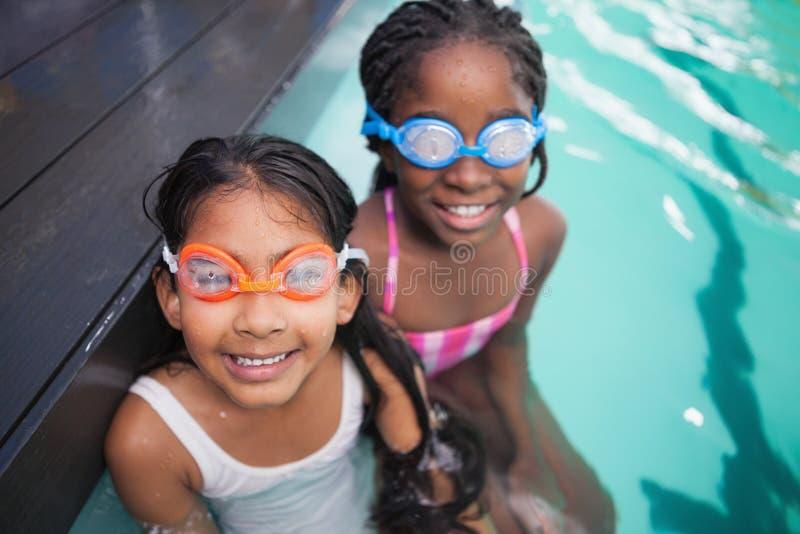 Gulliga små ungar som sitter poolsiden royaltyfri fotografi