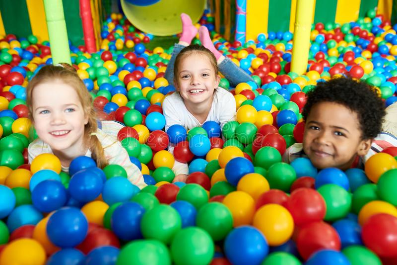 Gulliga små ungar som spelar i Ballpit arkivfoto