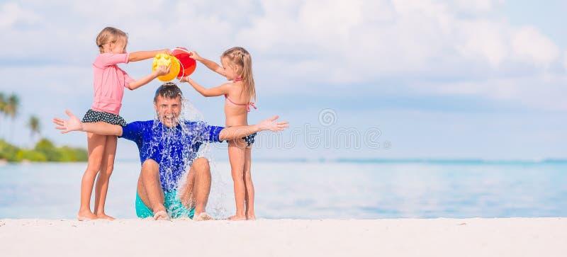 Gulliga sm? flickor som har gyckel med farsan p? den vita stranden royaltyfria bilder
