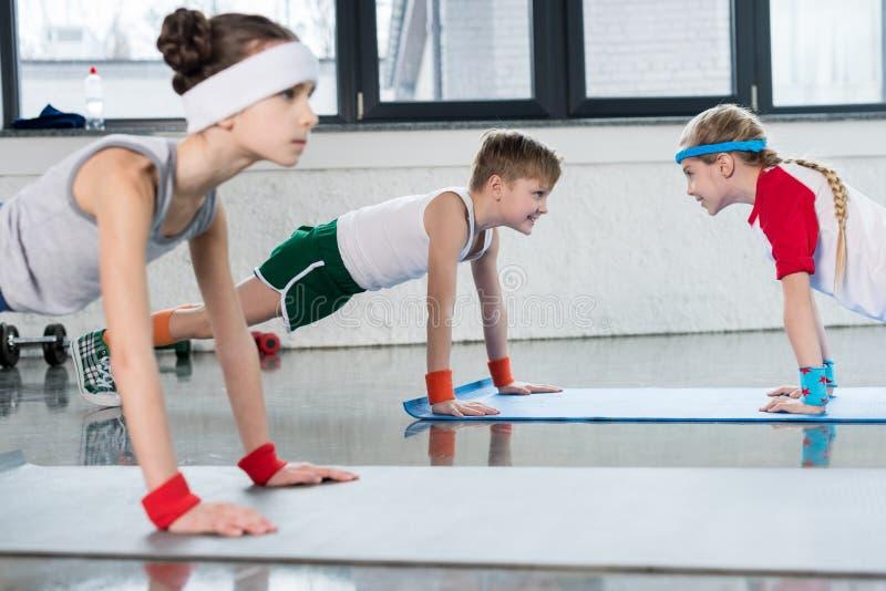 Gulliga sportiga ungar som övar på yogamats, i idrottshall och att le royaltyfria bilder