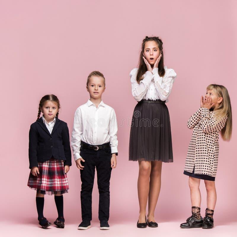 Gulliga stilfulla barn på rosa studiobakgrund De härliga tonåriga flickorna och pojken som tillsammans står arkivbilder