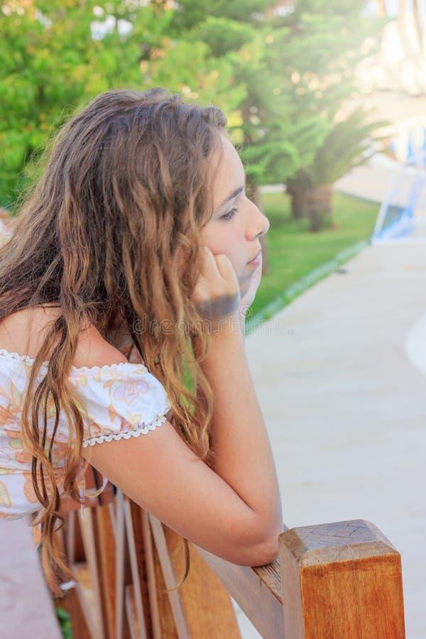 Gulliga tonåriga för flicka ställningar och drömmar hänsynsfullt på bron vid pölen arkivbild