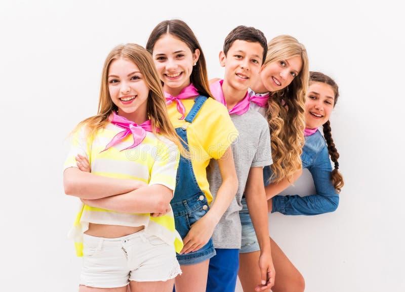 Gulliga tonårs- barn som en och en står fotografering för bildbyråer