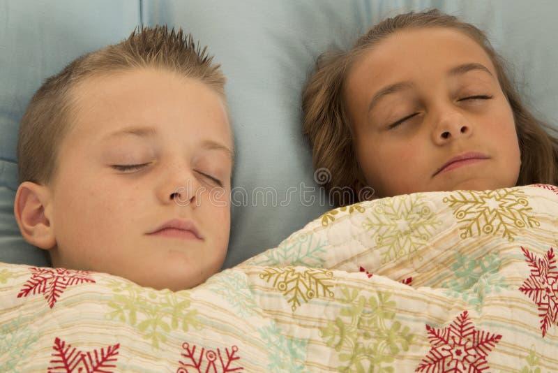 Gulliga unga barn sovande med en kudde och en filt royaltyfria foton