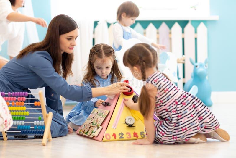 Gulliga ungar som spelar med det upptagna brädet i dagis Bildande leksaker för barn` s Trämodigt bräde royaltyfria foton