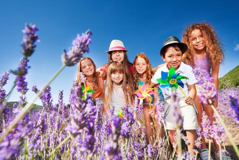 Gulliga ungar som spelar med små solar i lavendelfält royaltyfria bilder