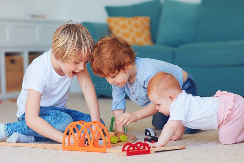 Gulliga ungar, syskon som spelar leksaker tillsammans på mattan hemma royaltyfri foto
