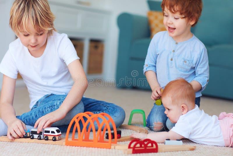 Gulliga ungar, syskon som spelar leksaker tillsammans p? mattan hemma arkivbilder