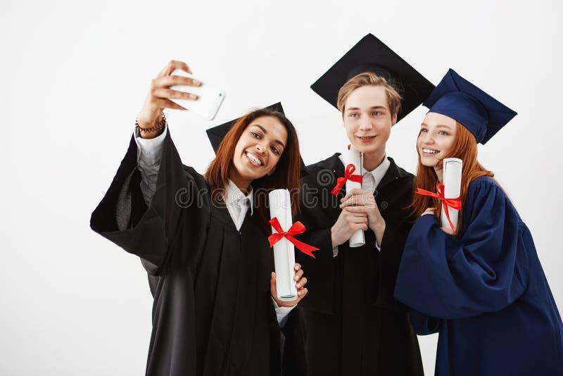 Gulliga vänner avlägger examen le hållande diplom som gör selfie över vit bakgrund royaltyfri fotografi