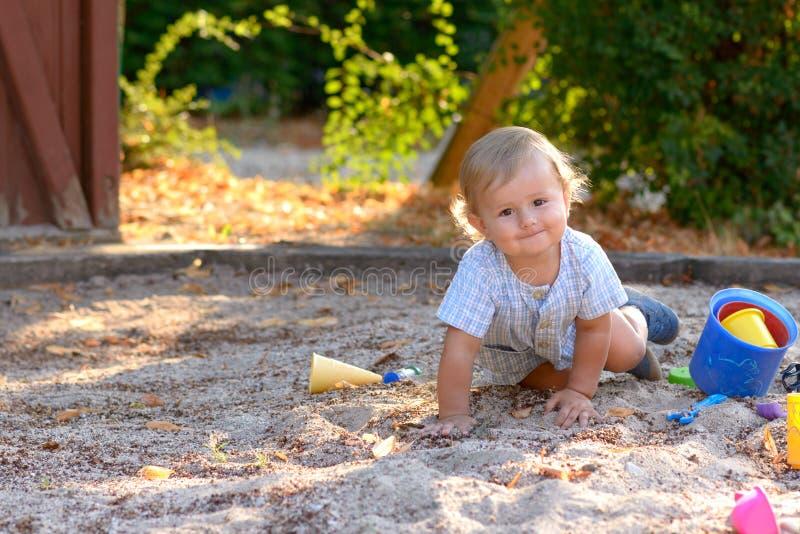 Gulliga vakna små behandla som ett barn pojkekrypning i sand royaltyfria foton