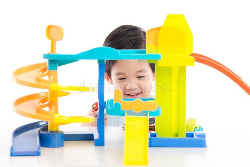 Gulligt asiatiskt barn som spelar leksakbilar royaltyfri bild