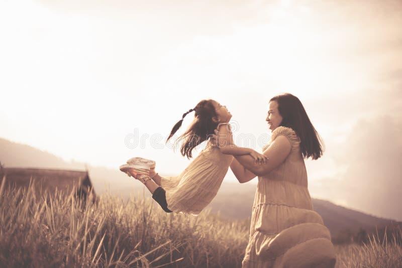 Gulligt asiatiskt barnflickaleende och gyckel medan moder som rymmer hennes unge royaltyfri fotografi