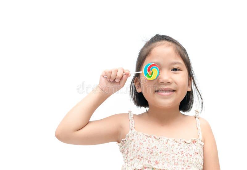Gulligt asiatiskt flickaleende med den isolerade godisen arkivbilder