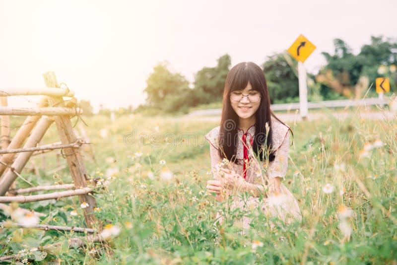 Gulligt asiatiskt flickaleende på fältet för blomma för änggräs royaltyfri bild