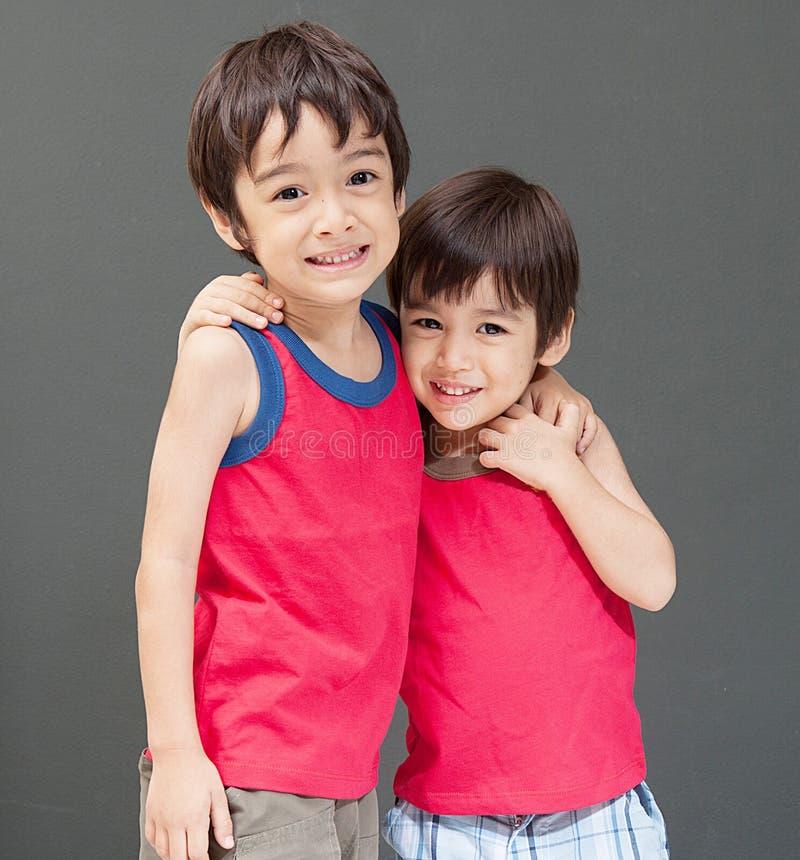 Gulligt asiatiskt le för sibling som är lyckligt arkivfoton