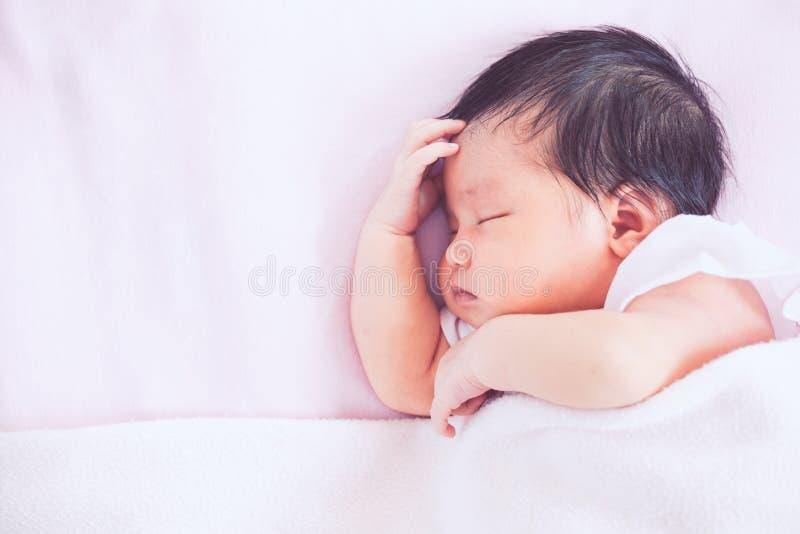 Gulligt asiatiskt nyfött behandla som ett barn flickan som sover i säng royaltyfria bilder