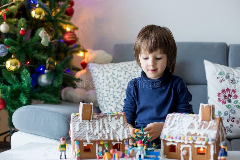 Gulligt barn, pojke som spelar med pepparkakahus arkivfoto