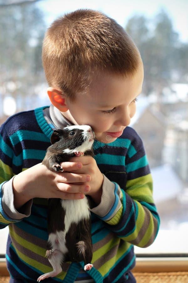 Gulligt barn som hemma spelar med hans husdjur försökskaninen royaltyfria bilder