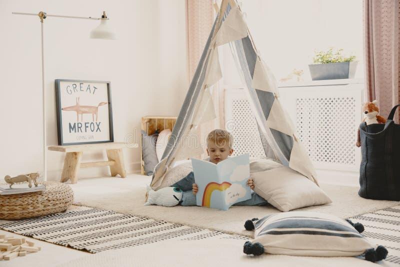 Gulligt barn som läser en bok som lägger på kuddarna i stilfullt scandinavian tält i lekrum royaltyfri fotografi