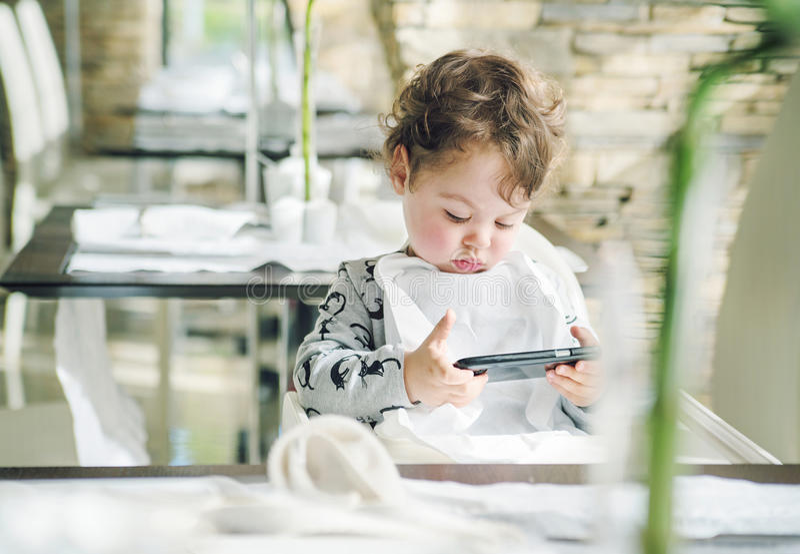 Gulligt barn som spelar lekar på med en smartphone royaltyfri bild