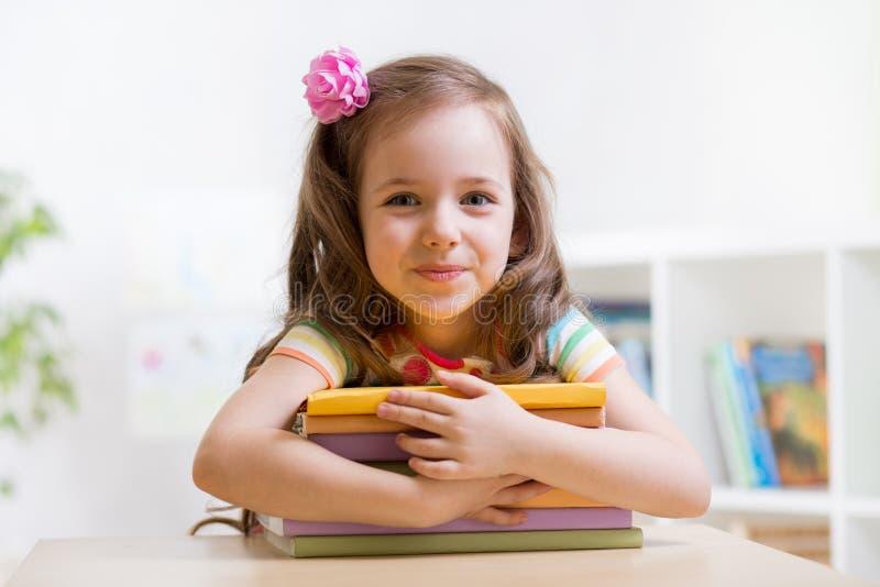 Gulligt barnflickaförskolebarn med böcker arkivbilder