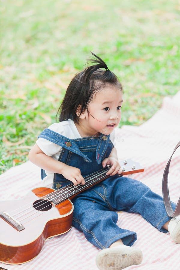 Gulligt behandla som ett barn årig lek för flicka 2 på picknickfilten royaltyfri fotografi