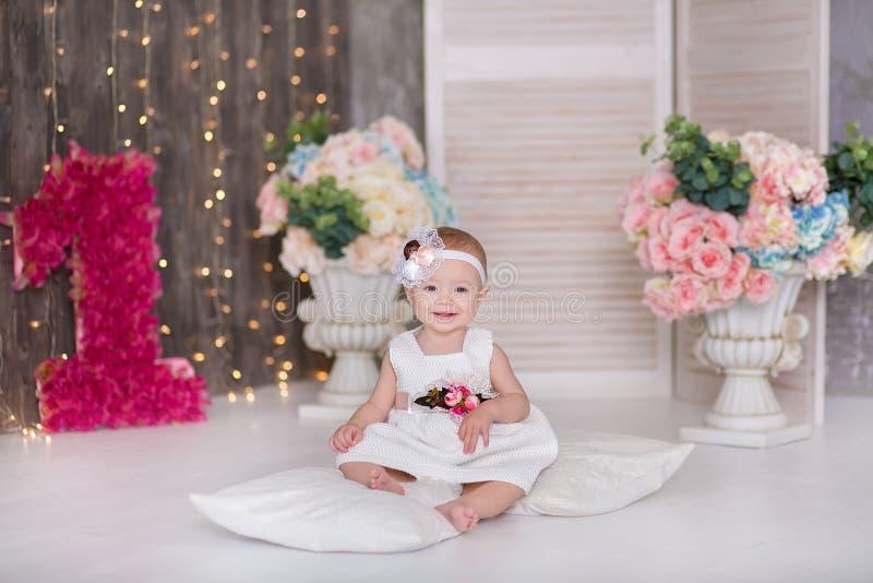 Gulligt behandla som ett barn årigt sammanträde för flicka 1-2 på golv med rosa ballonger i rum över vit isolerat caken för födel fotografering för bildbyråer