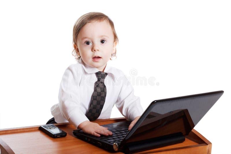Gulligt behandla som ett barn affärsmannen som fungerar på hans bärbar dator arkivfoto