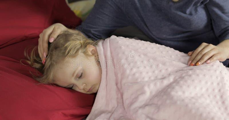 Gulligt behandla som ett barn att sova p? s?ngen hemma E arkivbild
