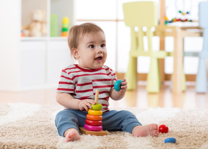 Gulligt behandla som ett barn att spela med pyramidleksaken i barnkammare royaltyfria foton
