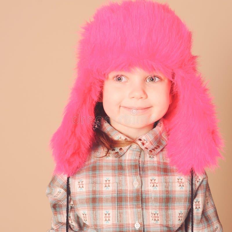 Gulligt behandla som ett barn den bärande pälshatten för flickan arkivbild