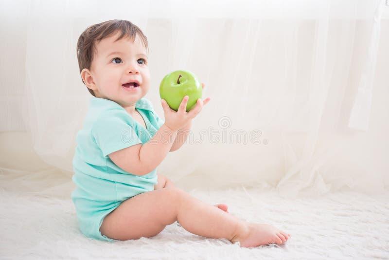 Gulligt behandla som ett barn det gröna äpplet för tagandet arkivbild