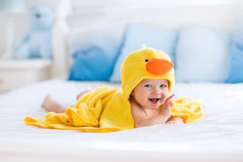 Gulligt behandla som ett barn efter badet i gul andhandduk arkivfoton