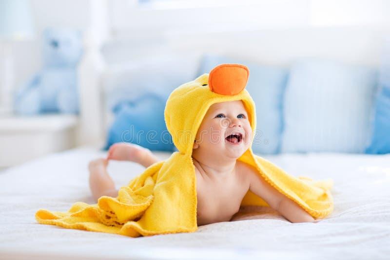 Gulligt behandla som ett barn efter badet i gul andhandduk fotografering för bildbyråer