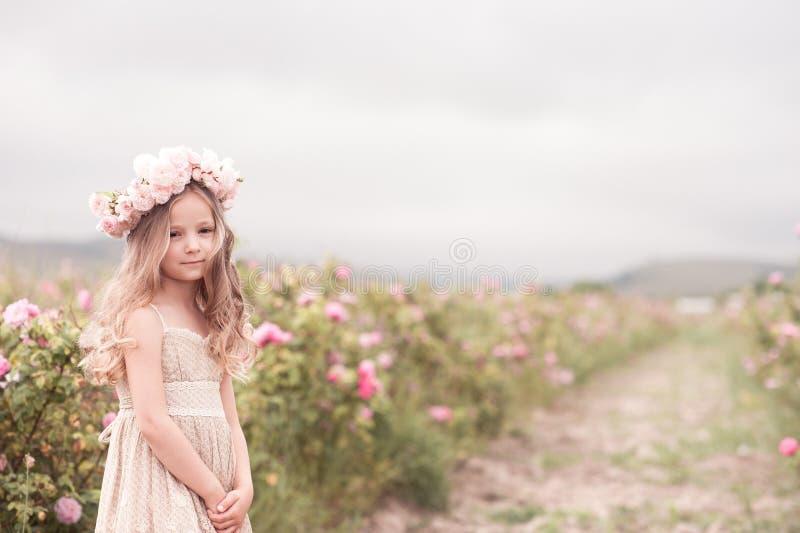 Gulligt behandla som ett barn flickaanseendet i rosträdgård arkivbild