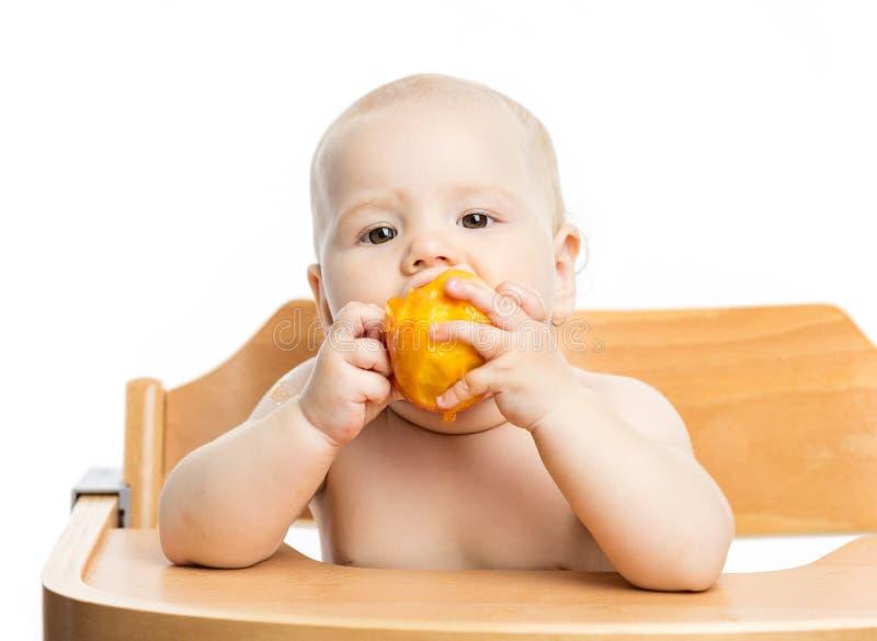 Gulligt behandla som ett barn flickan som äter persikan, medan sitta i hög stol royaltyfria bilder