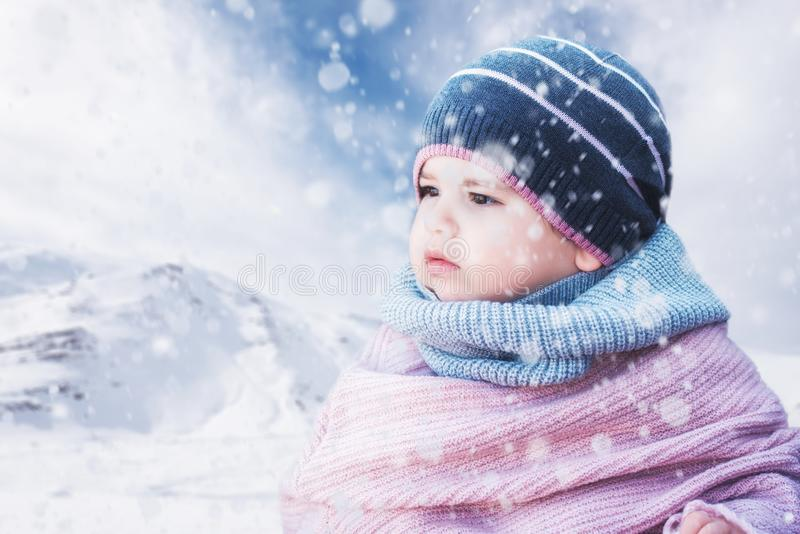 Gulligt behandla som ett barn flickan som bär en varm vinterhatt och en färgrik hatt på en snöig bakgrund arkivfoto
