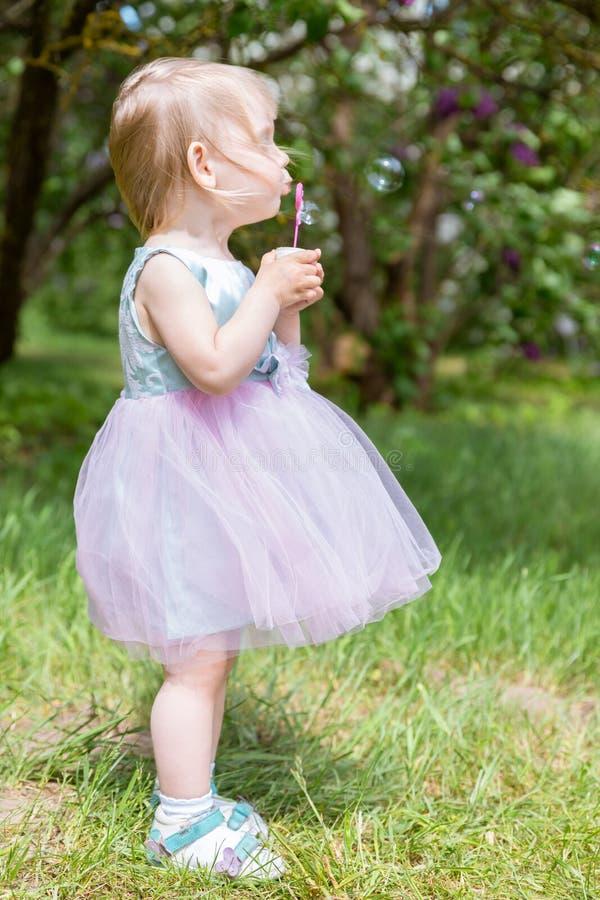 Gulligt behandla som ett barn flickan med bubblor i parkerar sommar f?r sn?ckskal f?r sand f?r bakgrundsbegreppsram royaltyfri bild