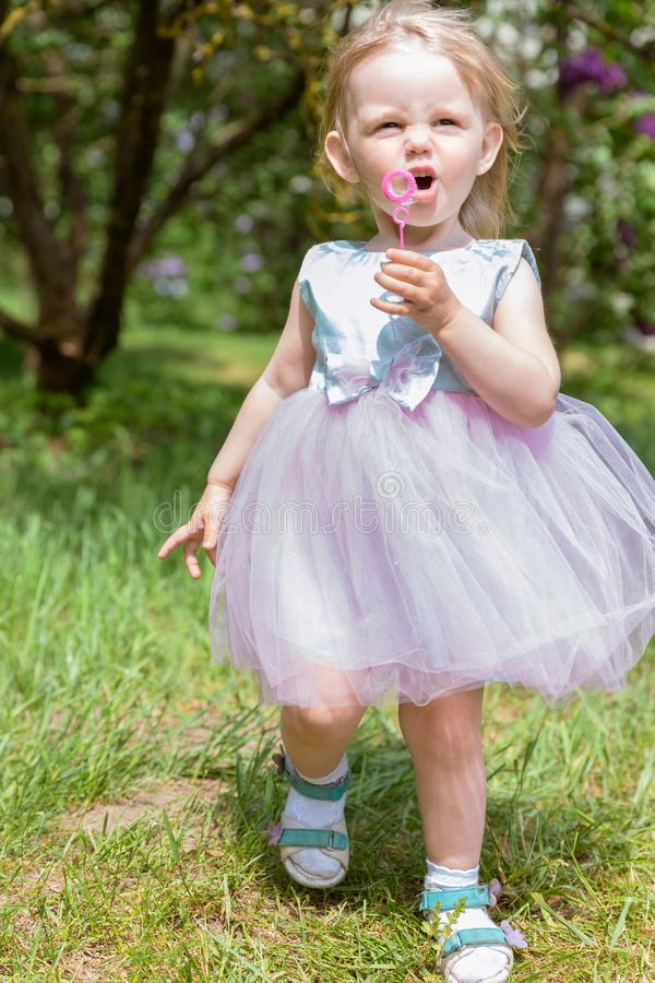 Gulligt behandla som ett barn flickan med bubblor i parkerar sommar f?r sn?ckskal f?r sand f?r bakgrundsbegreppsram royaltyfri foto